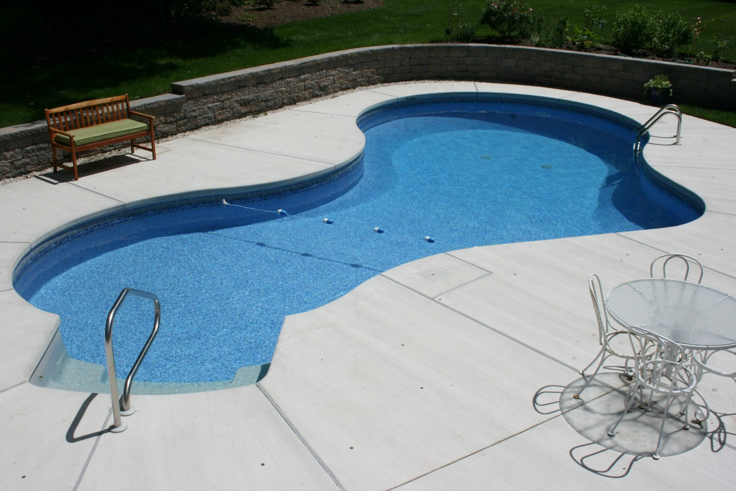 A Mountain Lake style pool featuring brushed concrete decking ...