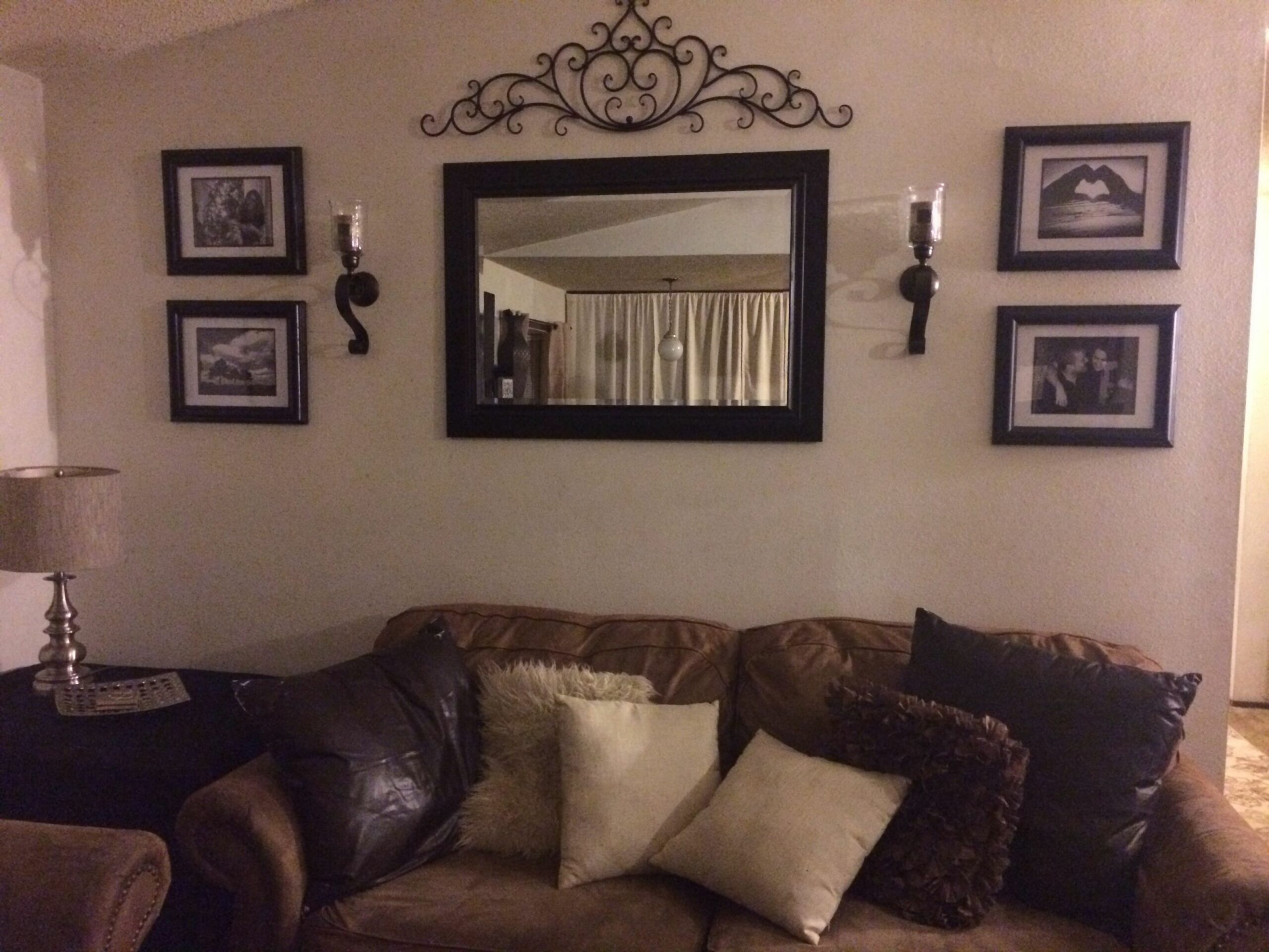 behind couch wall in living room mirror, frame, sconces, and metal ...
