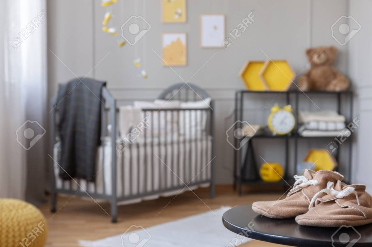 Beige toddler boots on black table in classy baby room with grey.