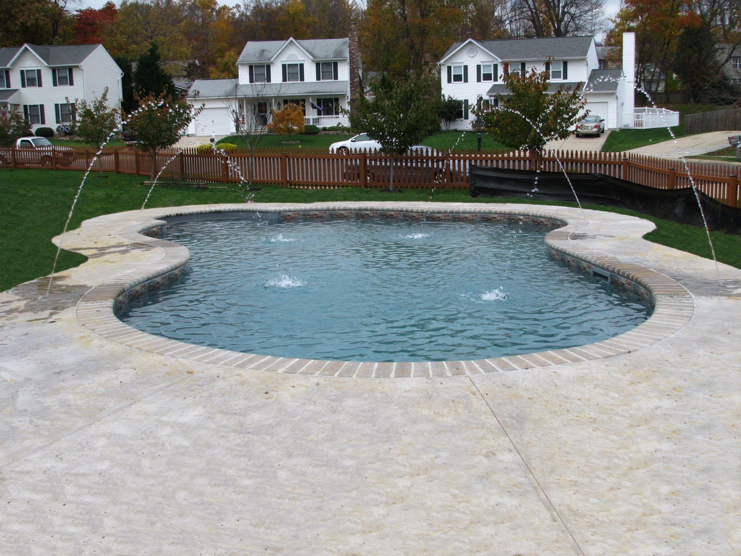 Freeform vinyl with Brick coping, stamped concrete and deck jets ..