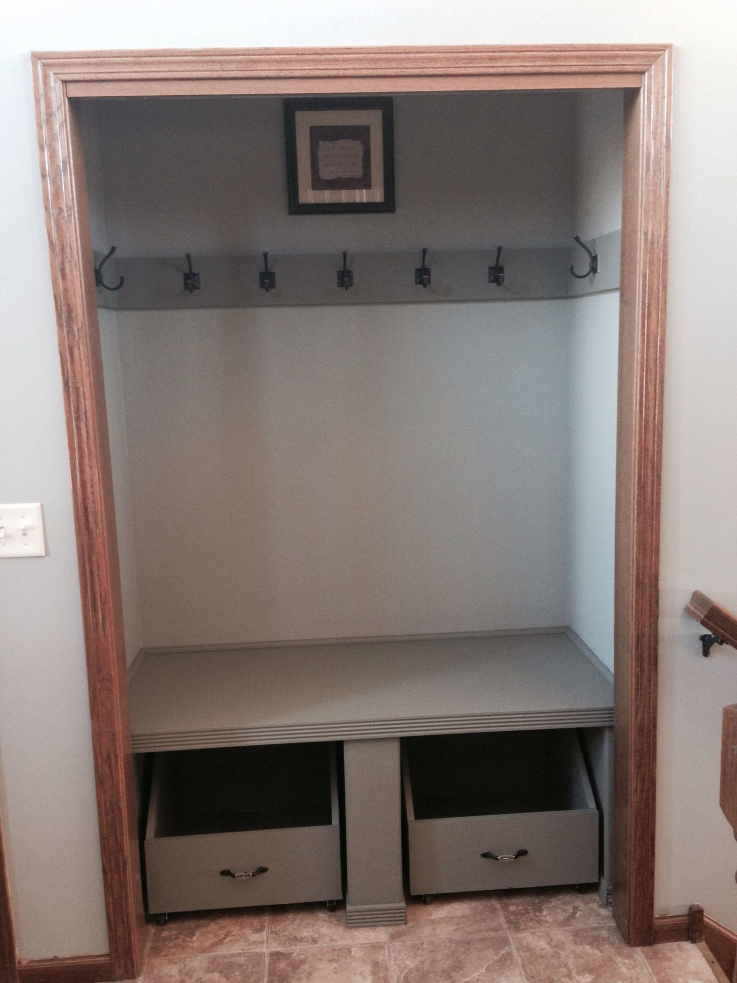 Front door closet with doors removed and shelf, hooks, and wheeled ...