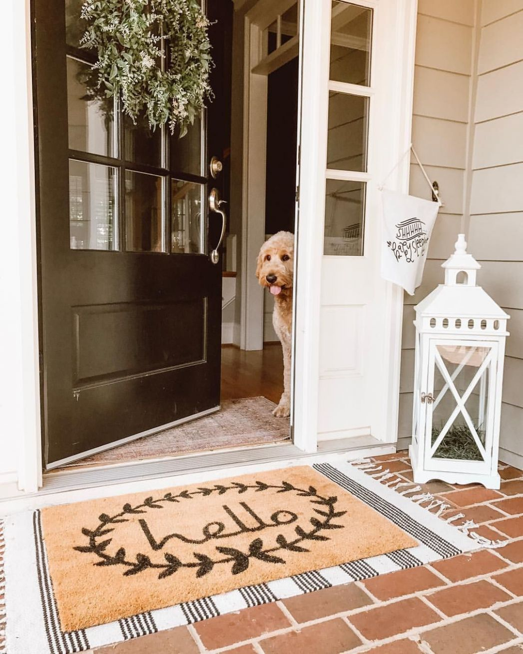 Layered doormats and an oversized lantern on the front porch ..