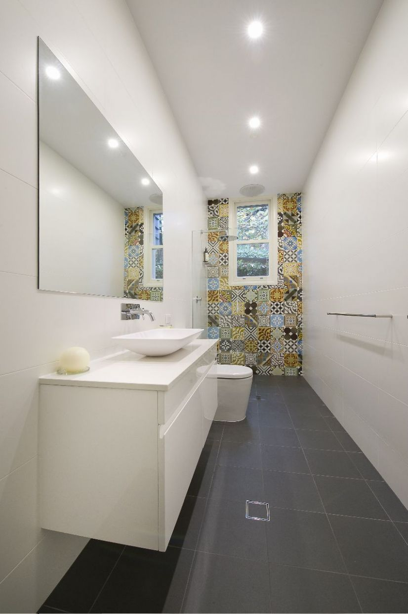 Long narrow bathroom with tiled feature wall around the window ..