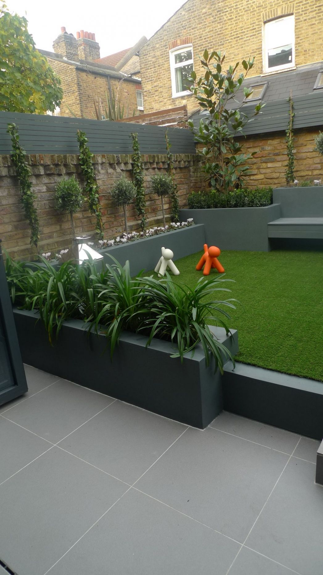 modern small low maintenance garden fake grass grey raised beds ...