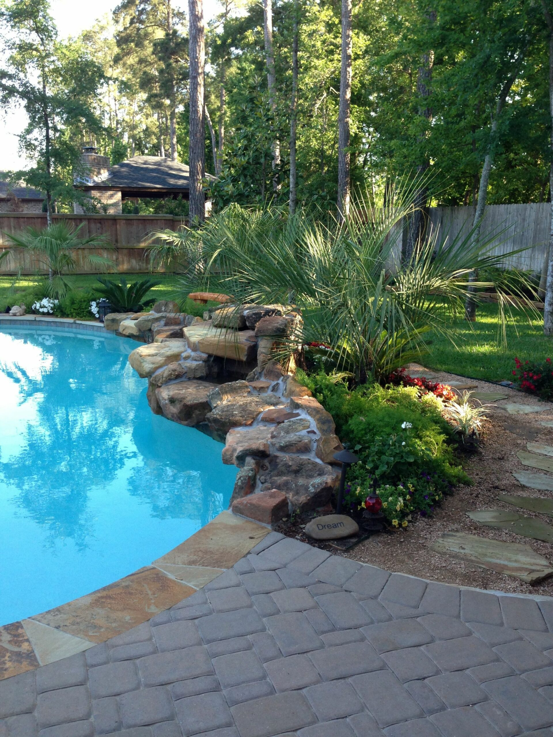 Pool Landscaping: rock waterfall in front of flowering plants ..