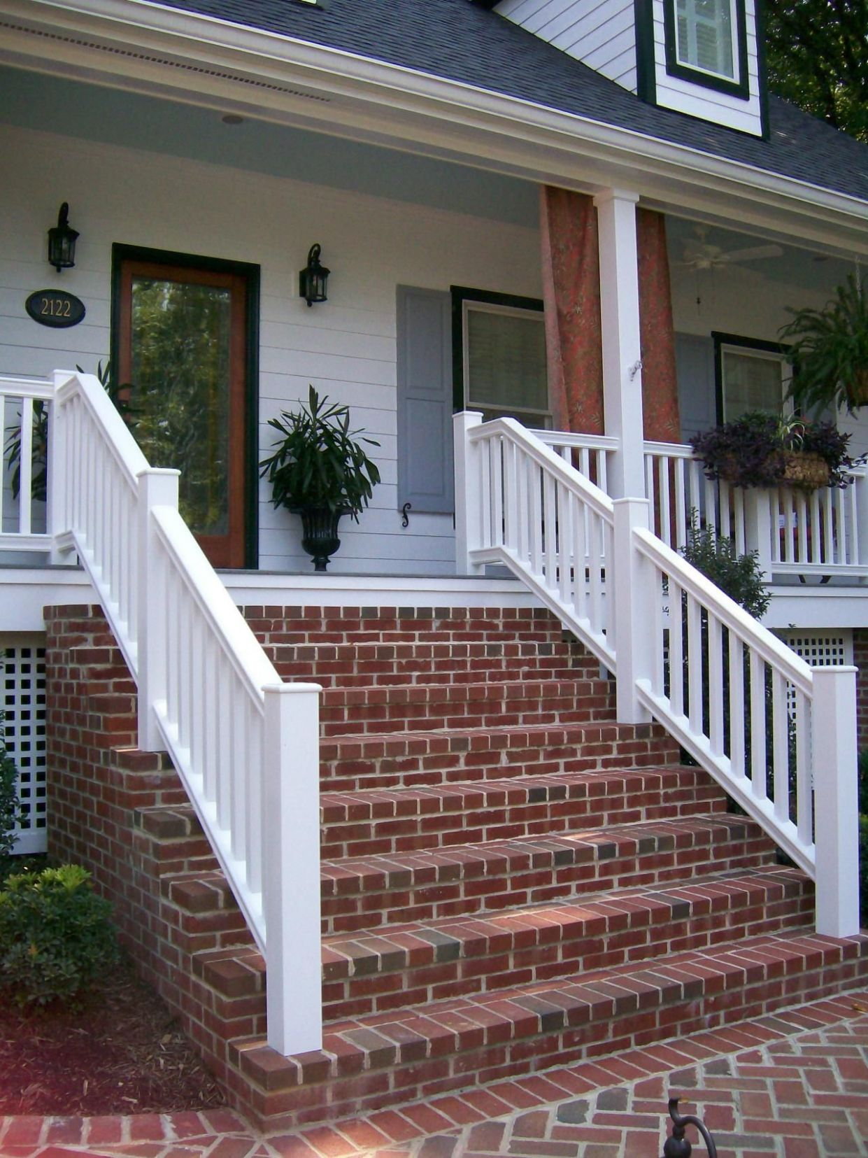 Red brick steps provide contrast to the bright white home exterior ...