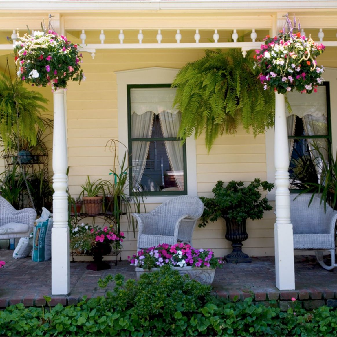 12 Front Porch Ideas and Décor for a More Welcoming Space - front porch decor with plants