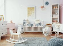 Bright baby room with white furniture, grey carpet on the floor..