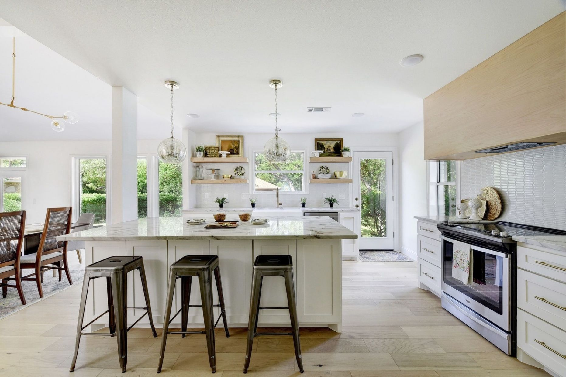 Bright white kitchen with wall of windows, sink at window ..