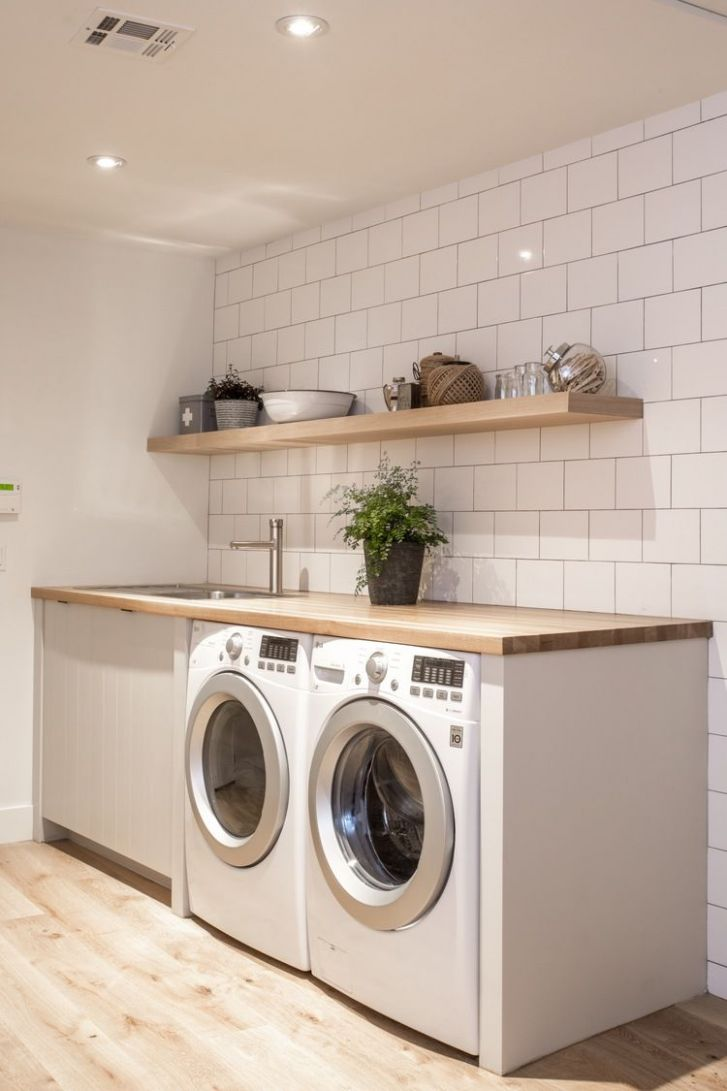 neutral, minimalist laundry room with open, wood shelving ..