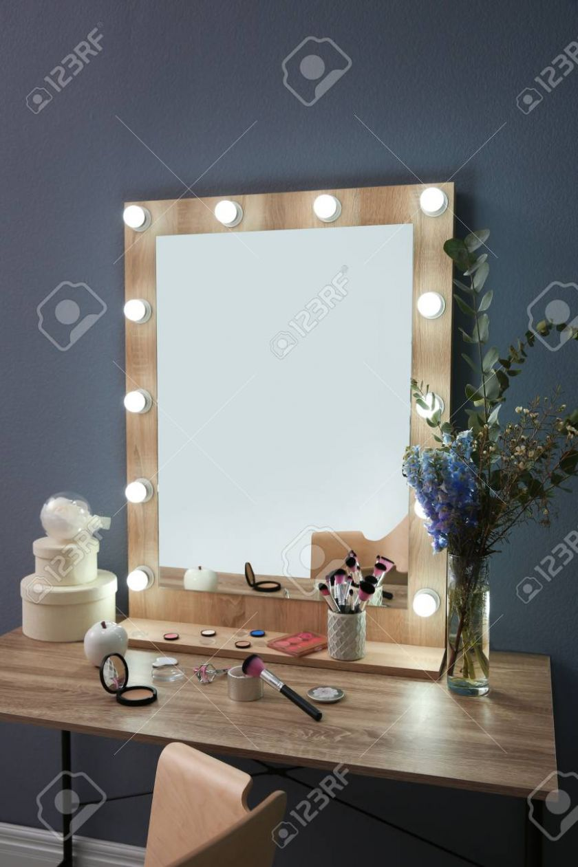 Table with beautiful mirror and cosmetics in modern makeup room - makeup room mirror