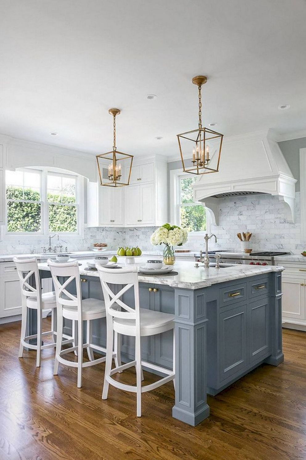 The windows on either side of the range hood add symmetry and ..