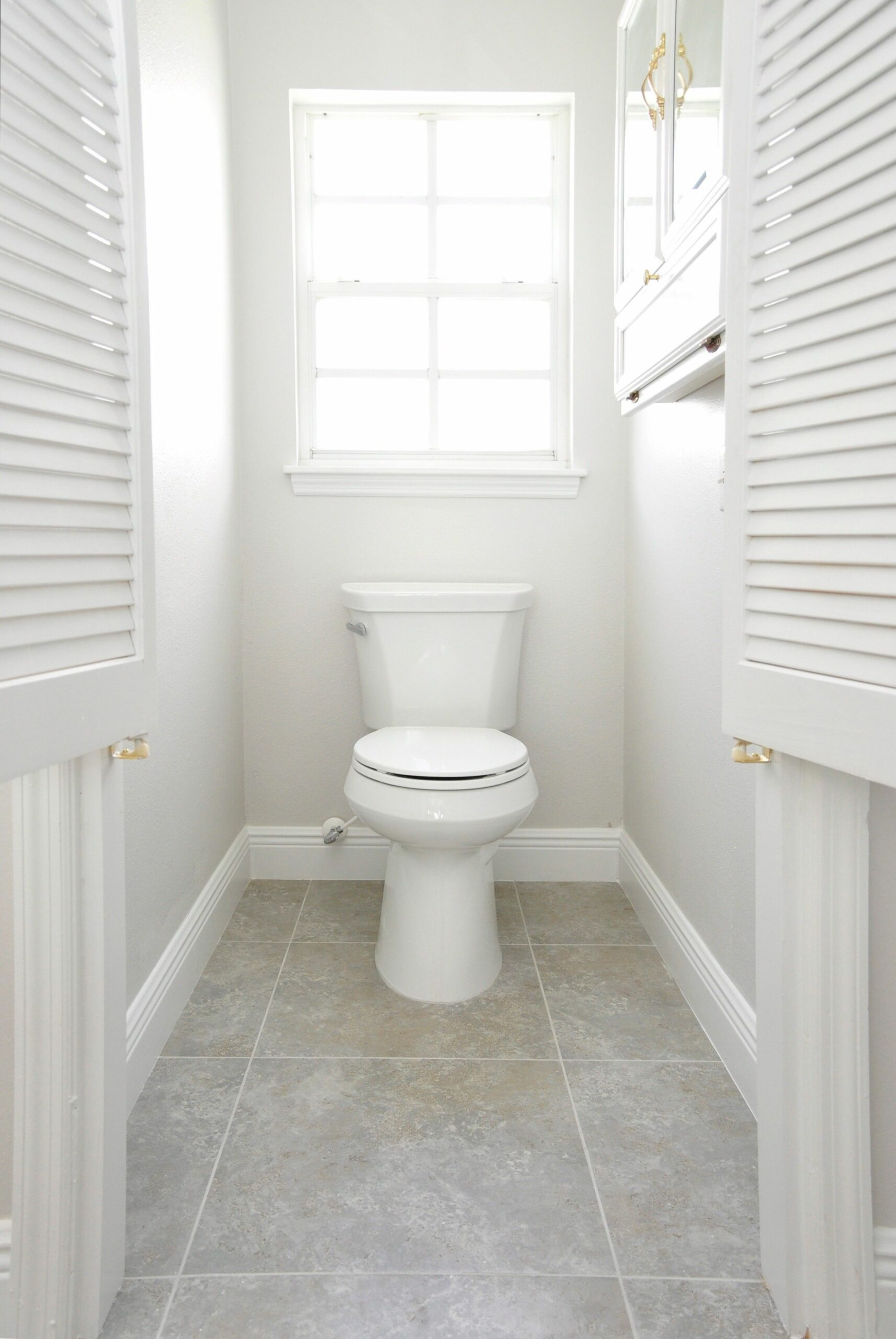white neutral toilet bathroom with window, medicine cabinet, and ..