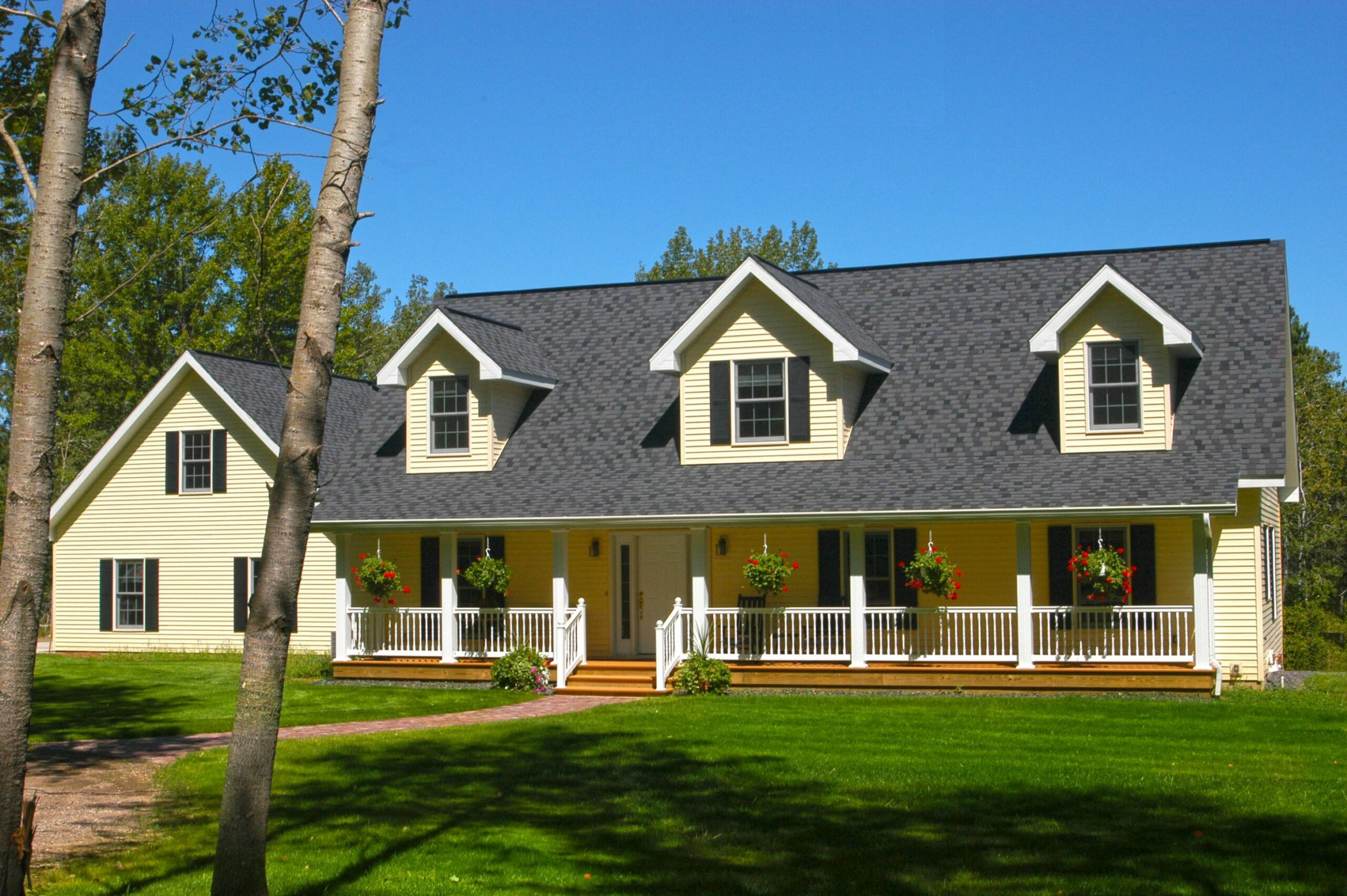 a cape cod style front with dormers and a long covered porch ...