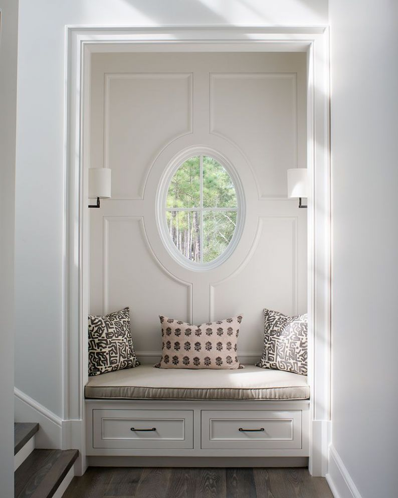 A small sitting nook is tucked below an oval window & matching ..
