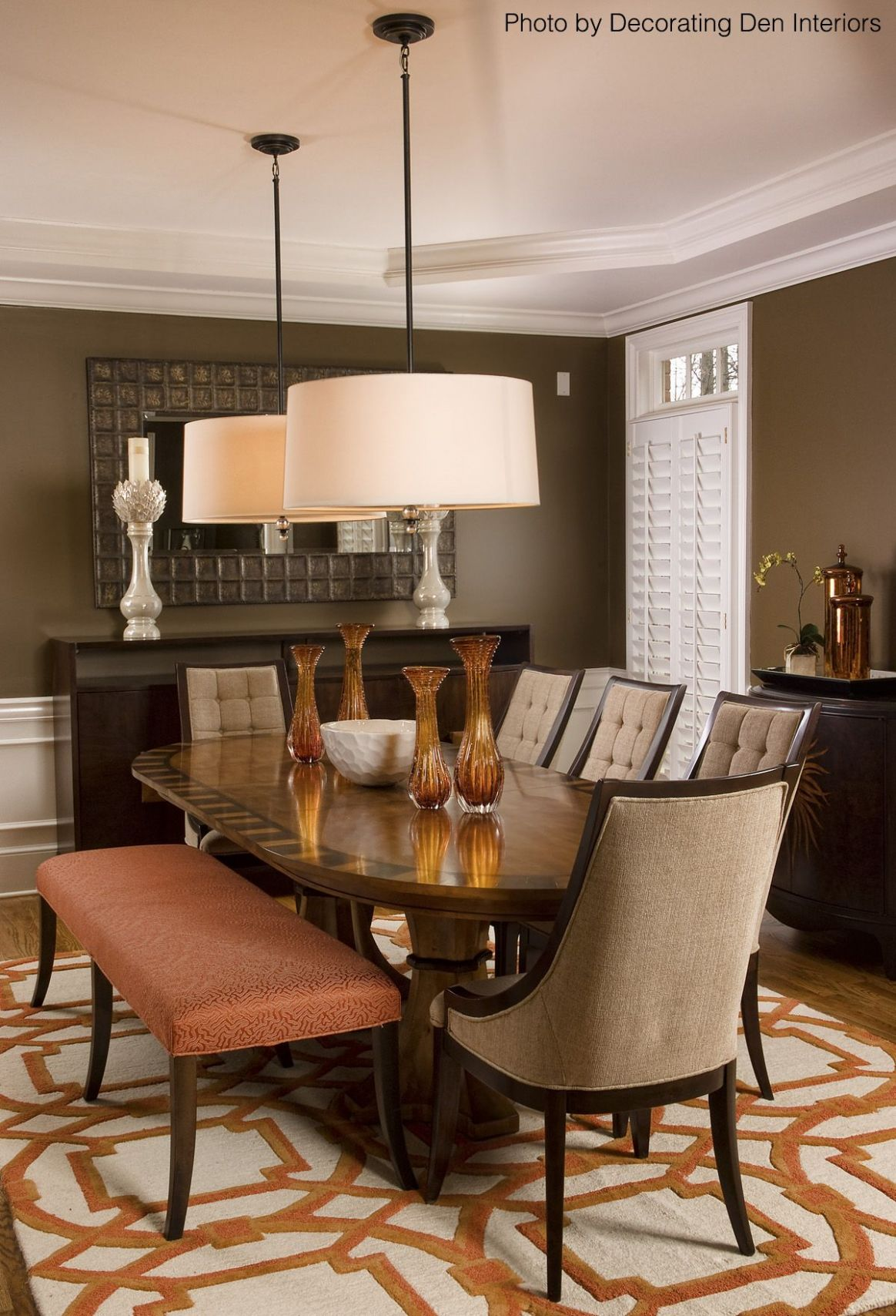 Brown dining room with an orange and white area rug, hardwood ...