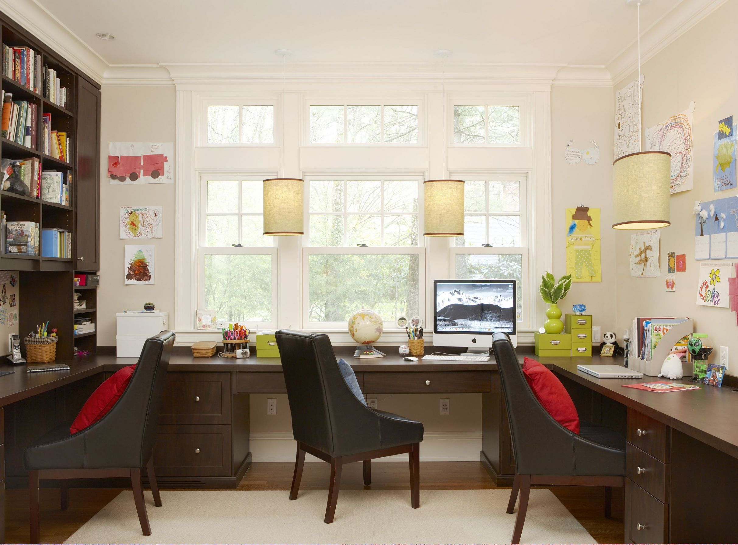 Built-in desks and dark wood bookcases make this study inviting ..