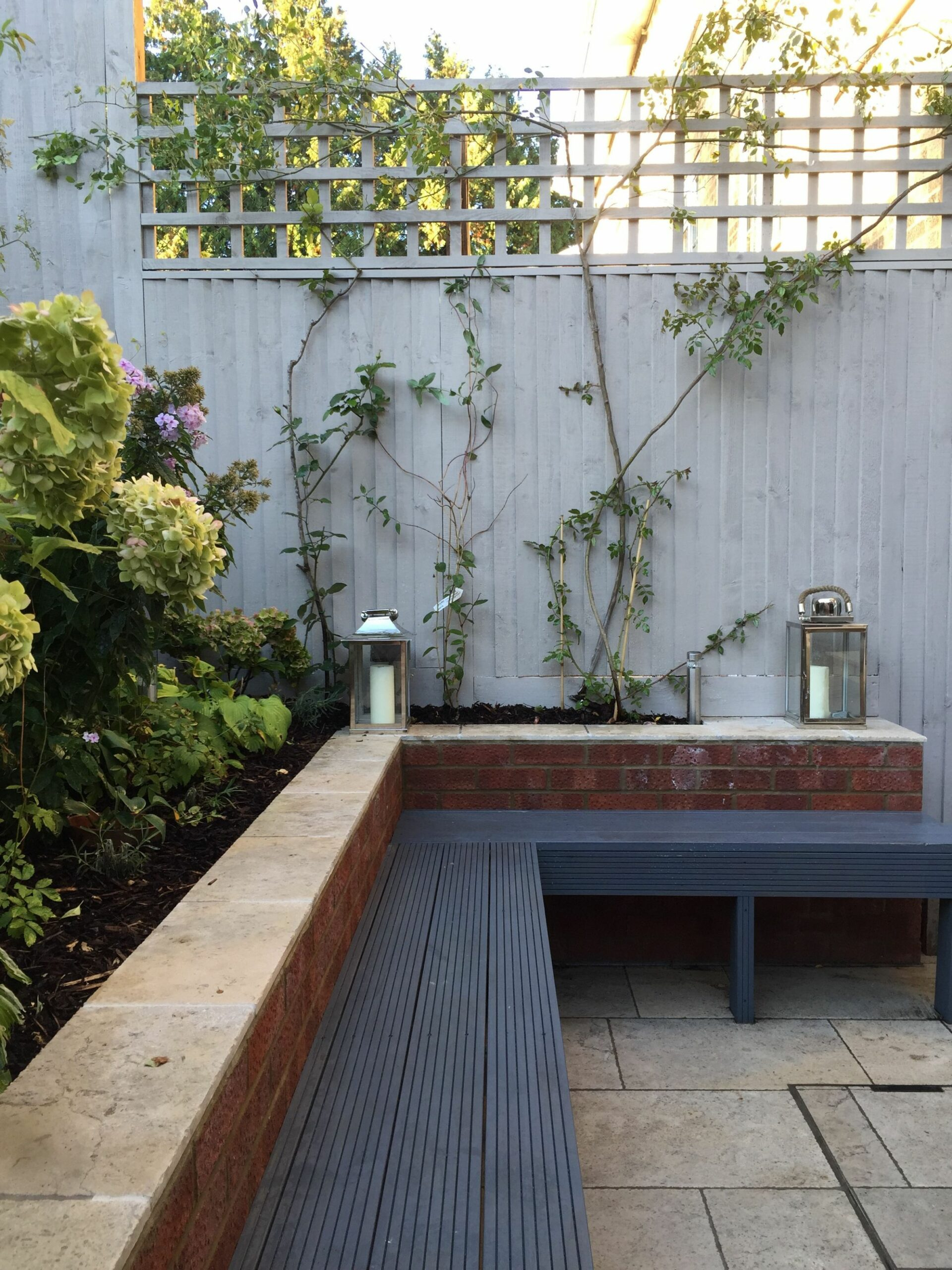 Built in garden bench seating painted in dark grey with ...