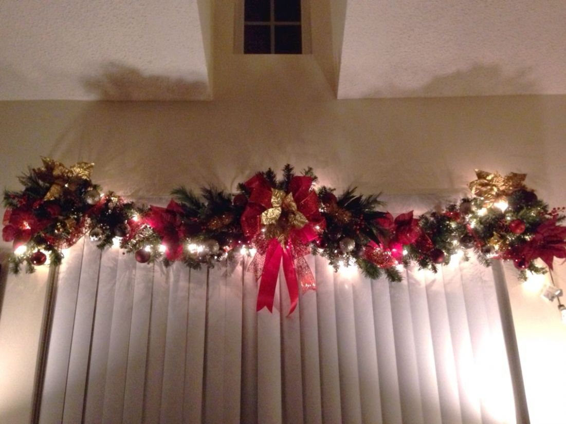 Christmas garland above windows, indoor, red and gold, lit ..