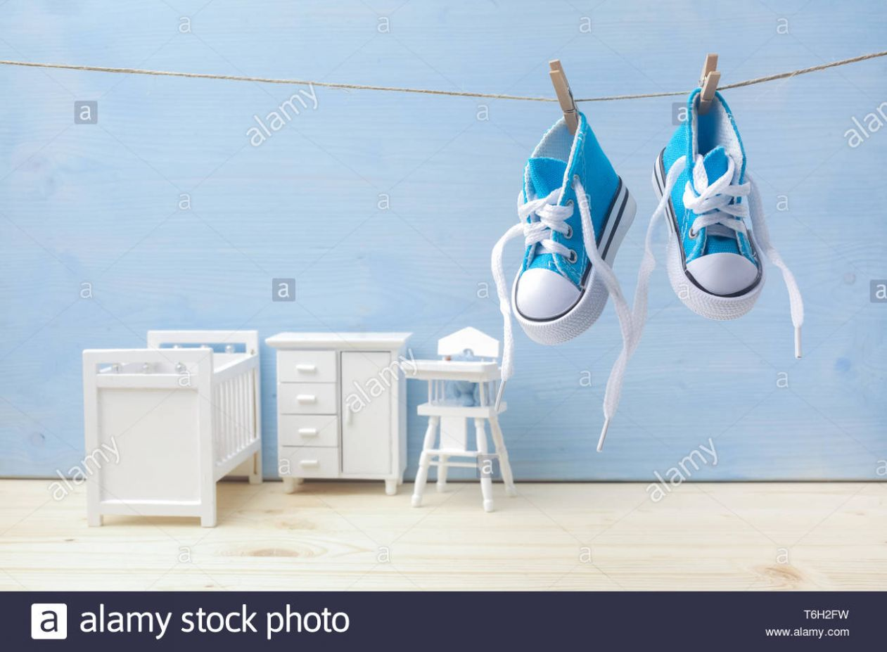 Cute little baby shoes hanghang on rope in baby room background ..