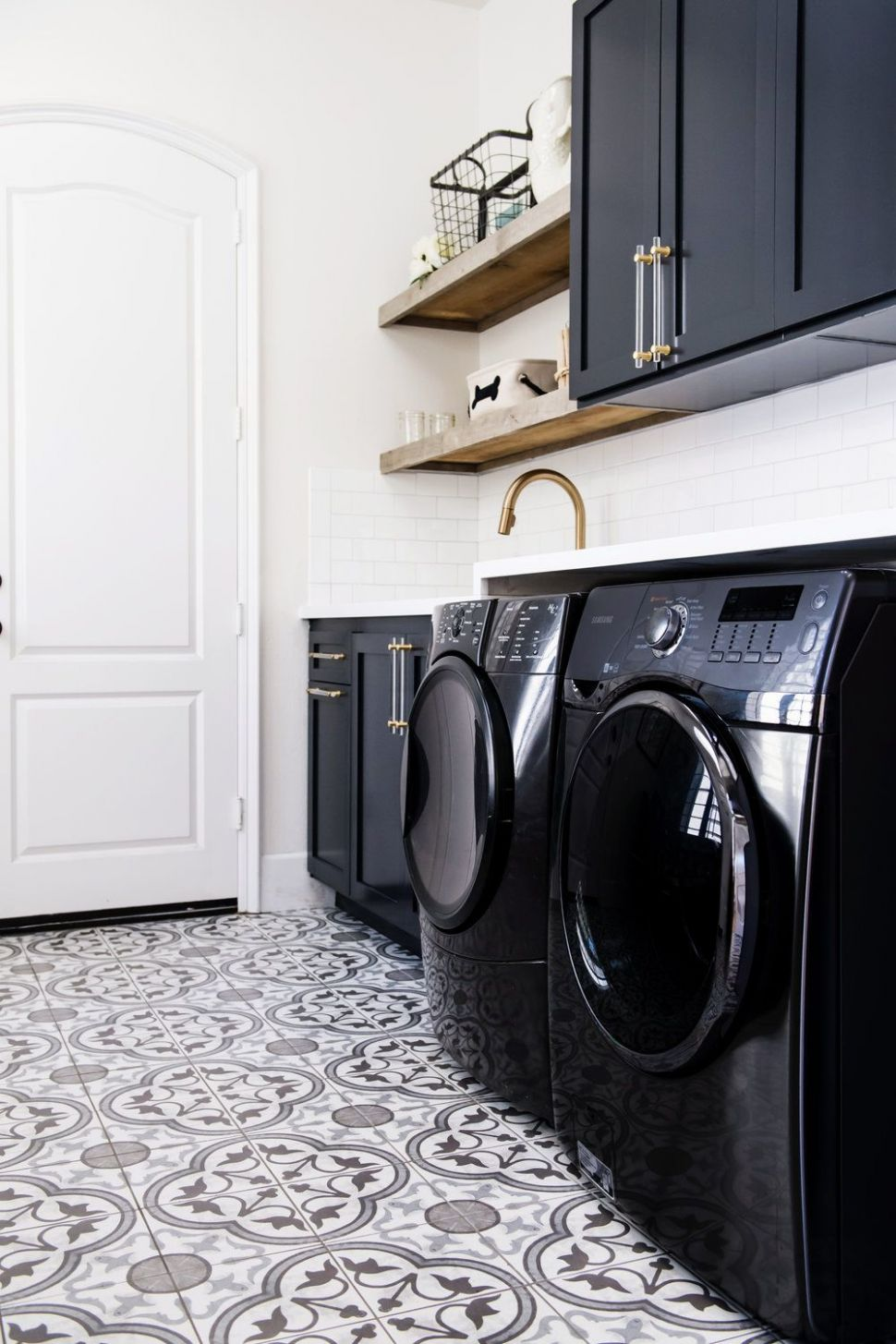 Dark cabinetry paired with black washer and dryers in this playful ...