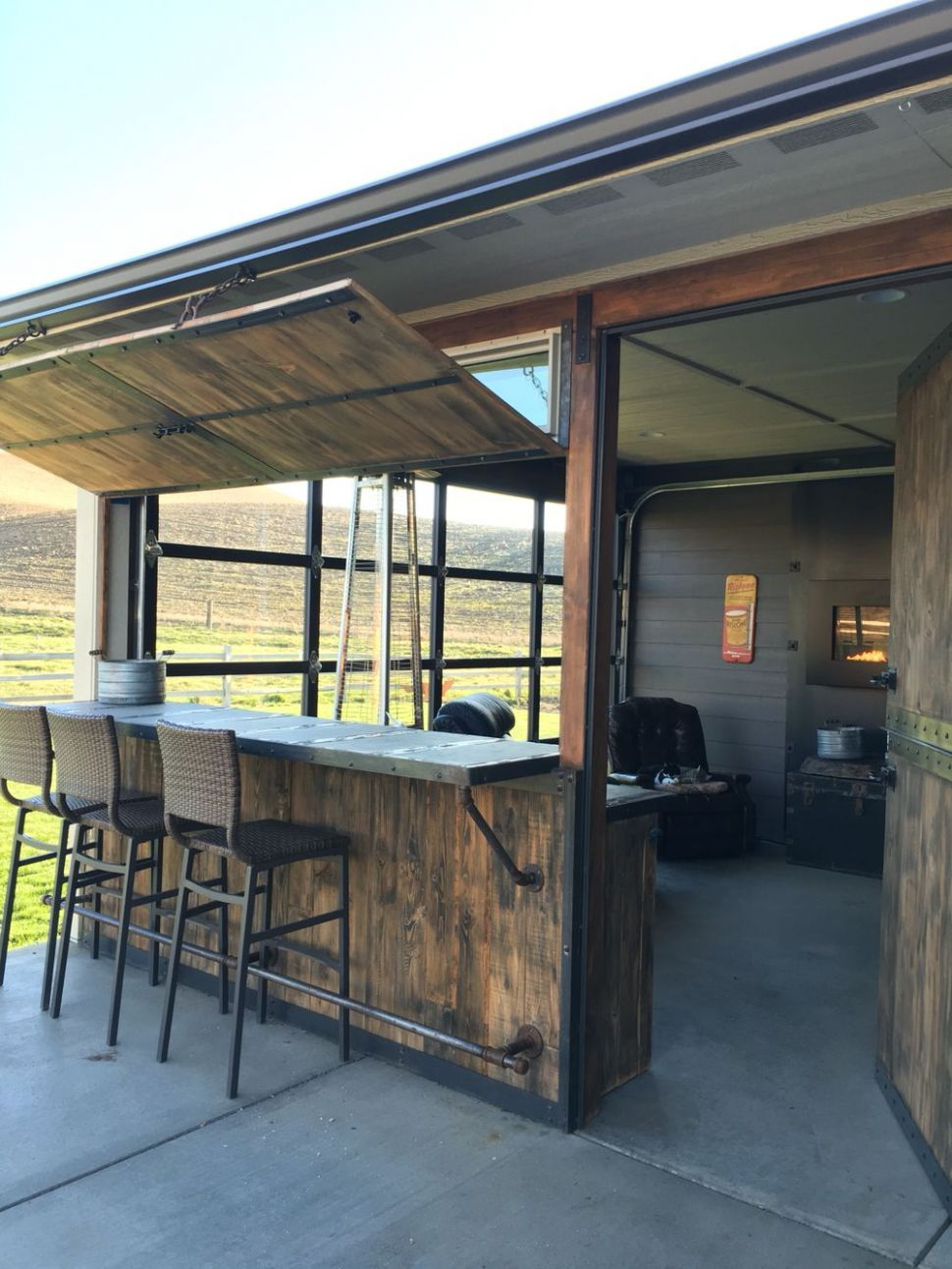 Fun Out door space with bar and sunroom. Glass garage door lets ..