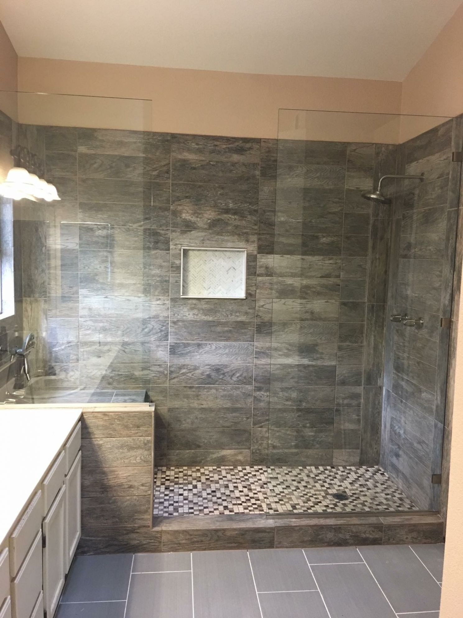 Large tile shower with double shower heads and bench seat. (With ..