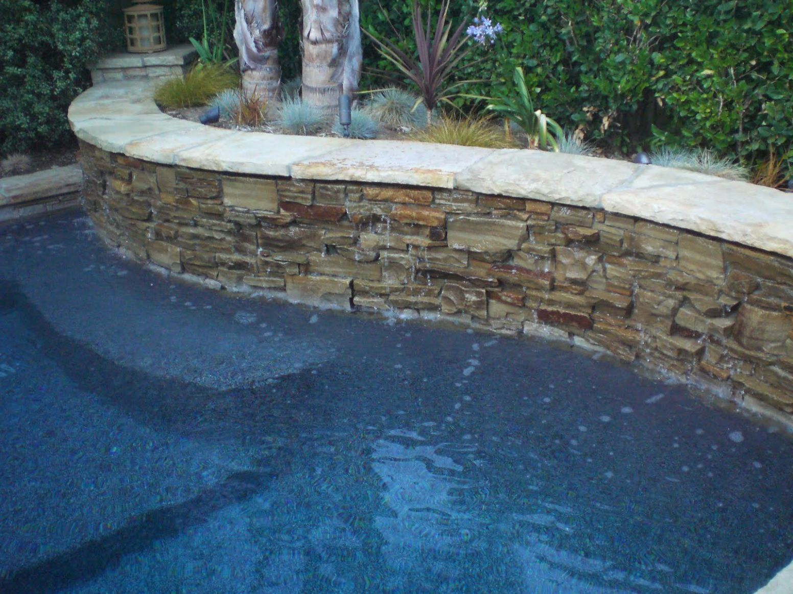 Pool with stacked stone retaining wall | Stone pool, Pool ..