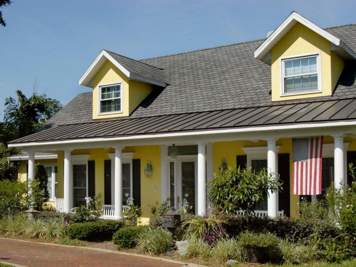 This bright yellow home exterior pops against the white molding ...